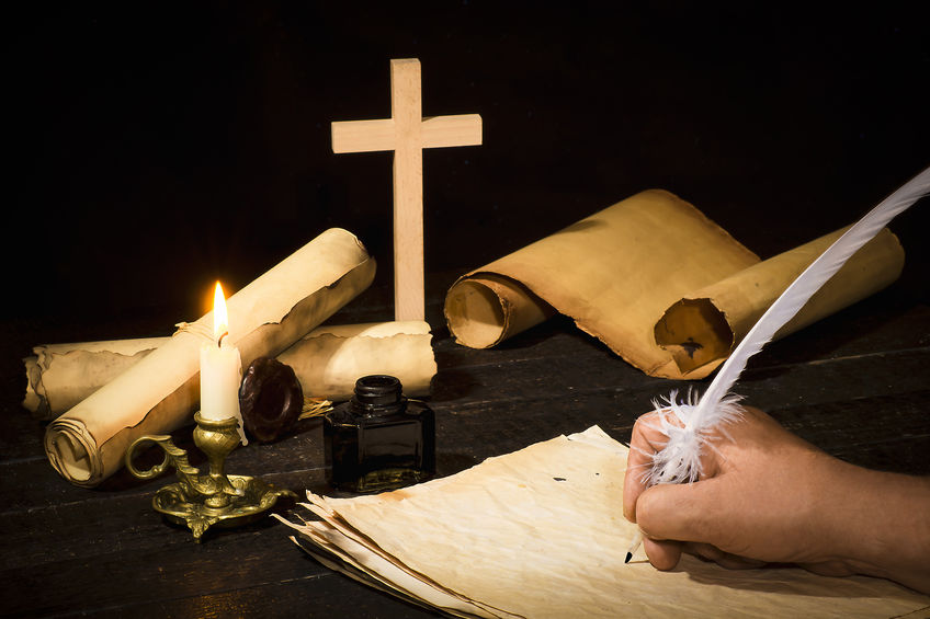 A hand writing with a pen on the background of papyrus scrolls, against the background of a candle and a cross, against a dark background.